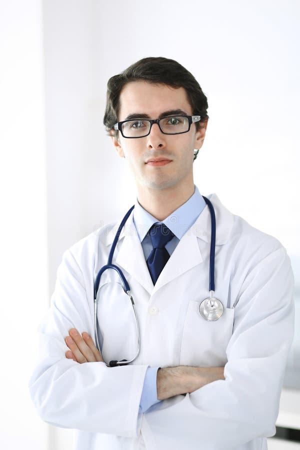 Doktorsmananseende som ?r rakt med korsade armar Perfekt medicinsk service i klinik Lycklig framtid i medicin och arkivfoton