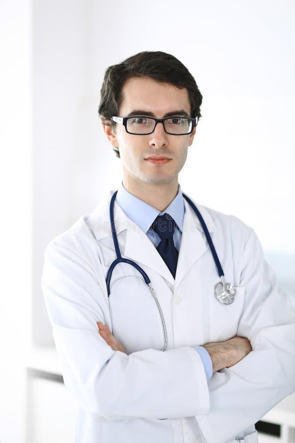Doktorsmananseende som ?r rakt med korsade armar Perfekt medicinsk service i klinik Lycklig framtid i medicin och royaltyfri bild