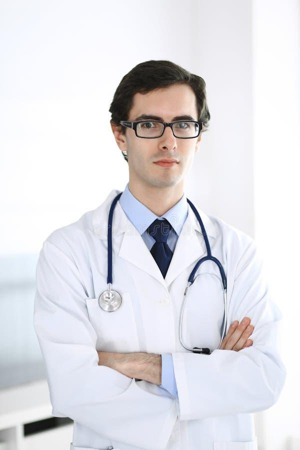 Doktorsmananseende som ?r rakt med korsade armar Perfekt medicinsk service i klinik Lycklig framtid i medicin och royaltyfri fotografi