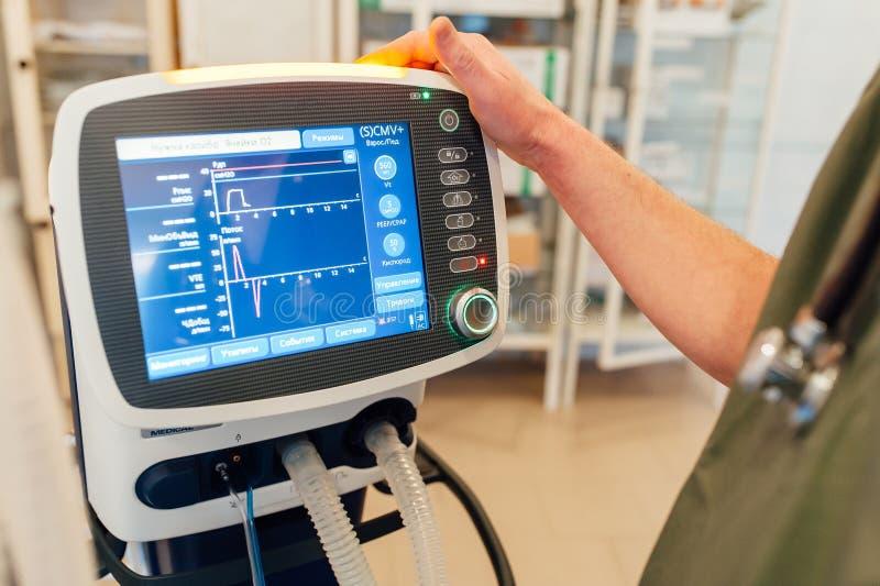 Doktorsmannen justerar den medicinska apparaten med bildskärmen royaltyfria foton