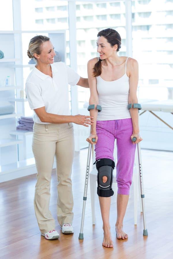 Doktorsportionkvinna som går med kryckor royaltyfri foto