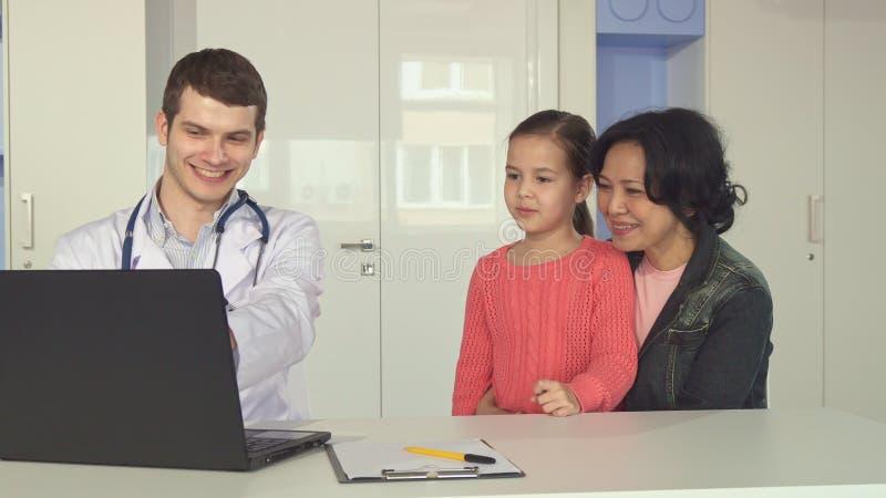 Doktorsshowliten flicka och hennes moder något på bärbara datorn arkivfoton