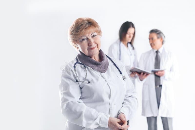 Doktorsterapeut f?r vuxen kvinnlig p? suddig bakgrund av kollegor royaltyfri foto
