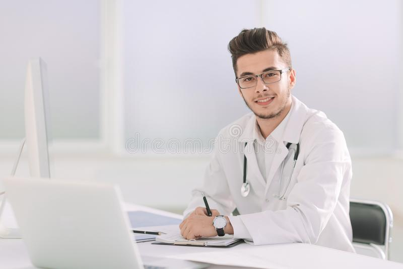 Doktorsterapeut som sitter på en tabell i hans kontor royaltyfria bilder