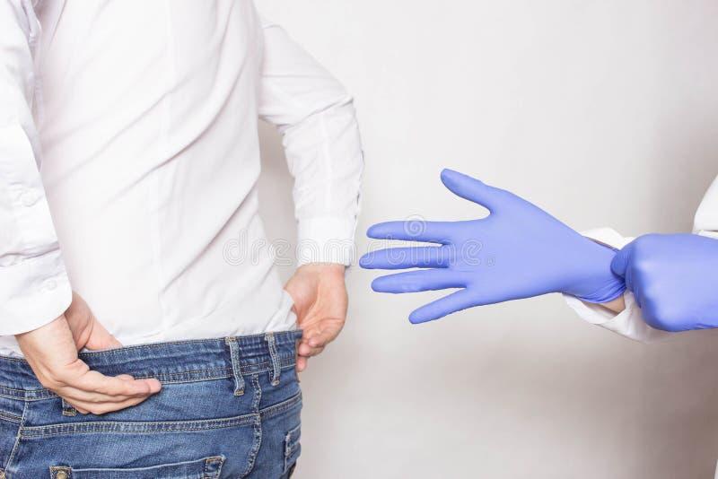 Doktorsurologen sätter en medicinsk handske på armen för att undersöka patientens prostata, prostatamassagen, lymfatisk dränering arkivbilder