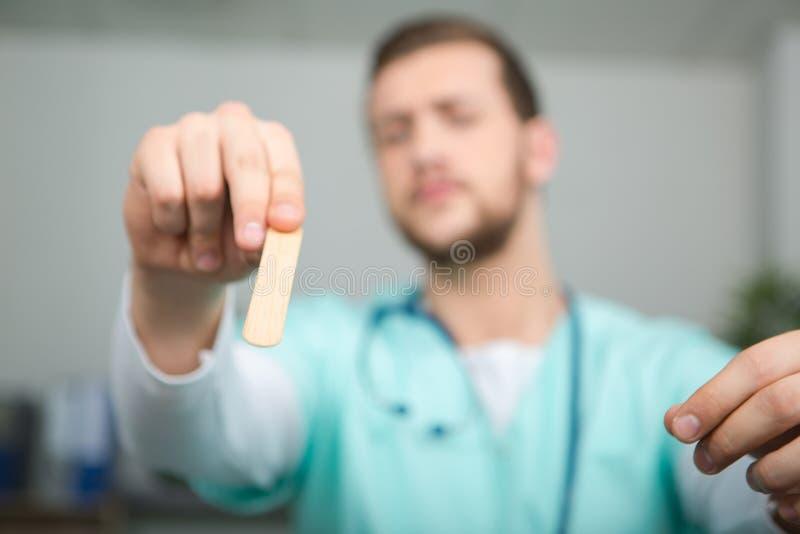 Doktorsvisning som klibbar murbruk på fingret royaltyfria foton