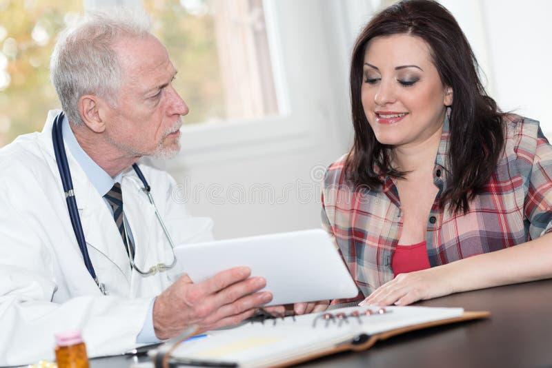 Doktorsvisningen anmäler på den digitala minnestavlan till patienten royaltyfria foton
