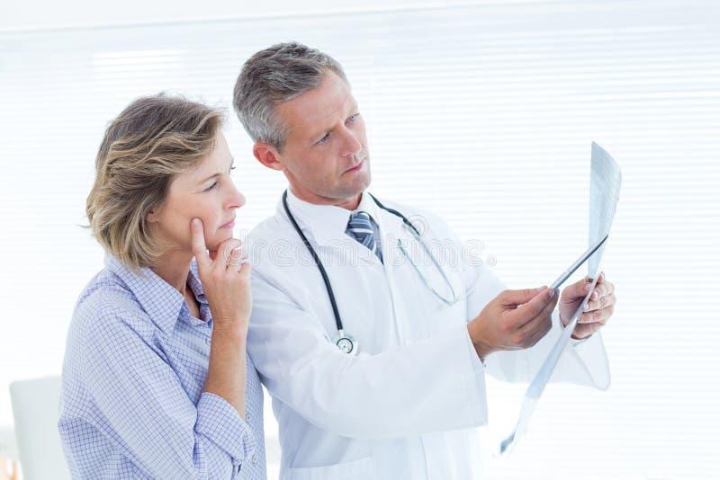 Doktorsvisningröntgenstråle till hans patient royaltyfri bild