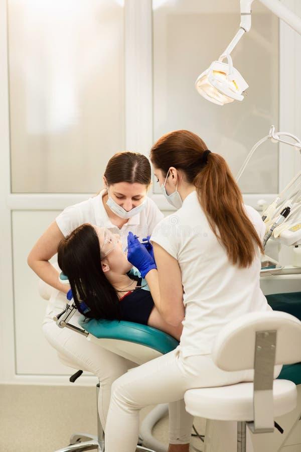 Doktorswhitassistent som behandlar tänder av patienten som förhindrar karies f?r handman f?r begrepp 3d tand f?r stomatology arkivfoton