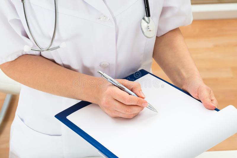 Doktorswriting på clipboarden arkivbilder
