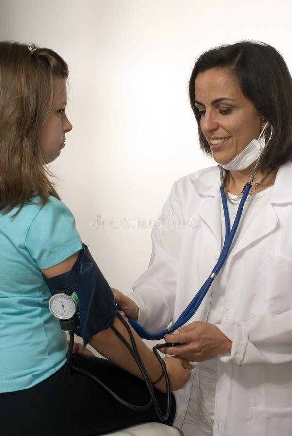 doktorze ciśnienie krwi dziewczyny bierze pionowe s obrazy stock