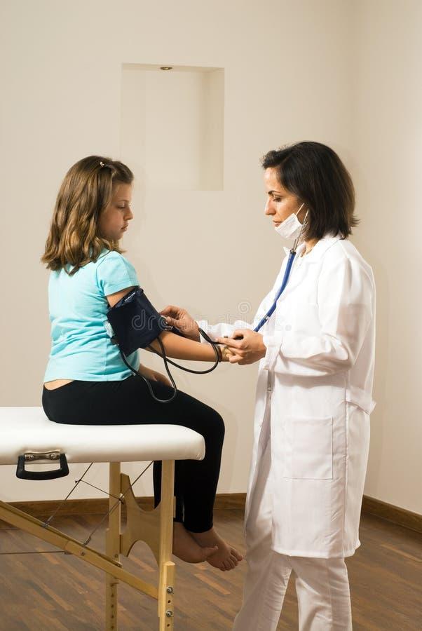 doktorze ciśnienie krwi dziewczyny bierze pionowe s fotografia stock