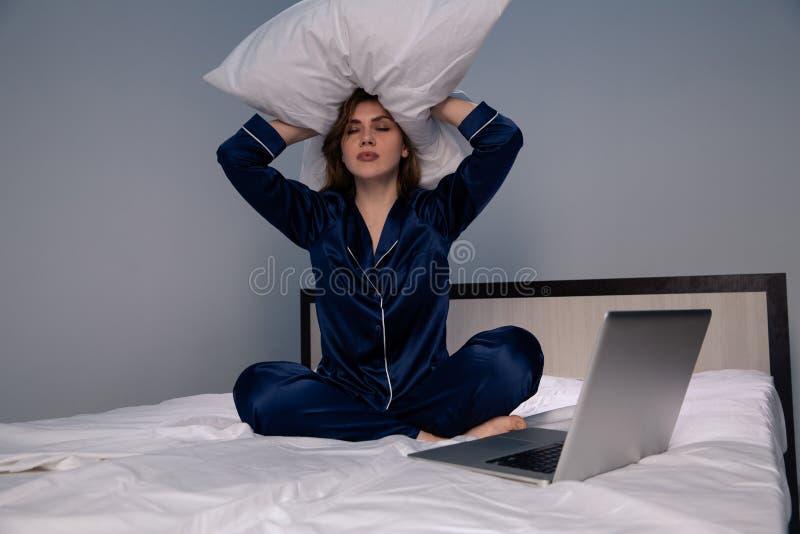 Dokuczająca kobieta w obsiadaniu w łóżku z poduszką na jej głowie obrazy royalty free