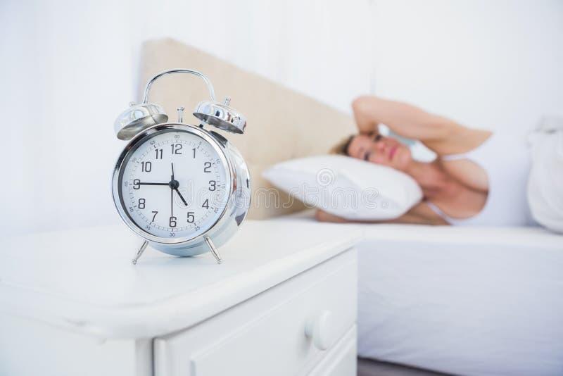 Dokuczająca kobieta zakrywa jej ucho od budzika hałasu w łóżku obrazy royalty free