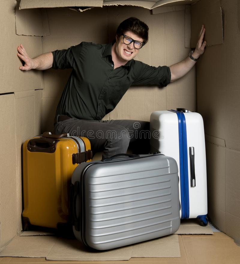 Dokuczająca młody człowiek czuciowa niewygoda wśrodku małego pokoju z bagażem zdjęcia royalty free