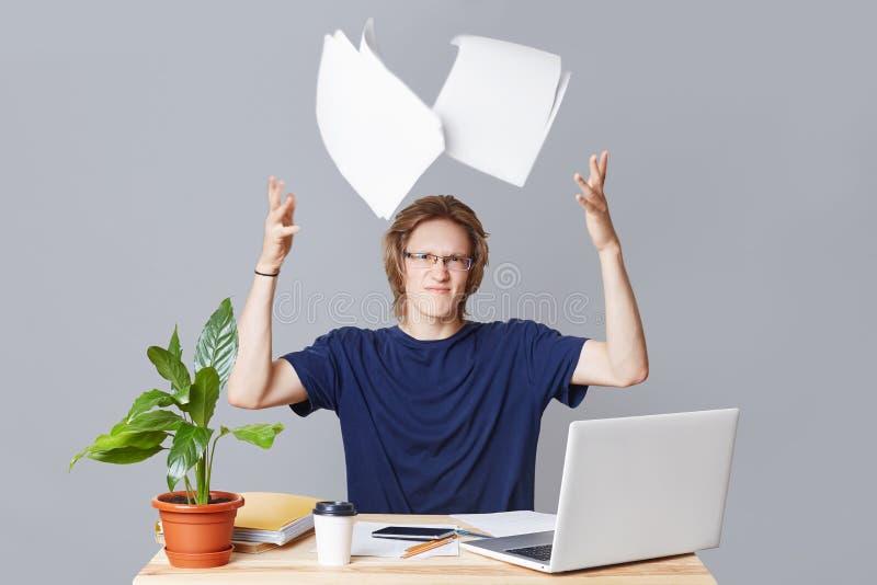 Dokuczający biznesmen kłopoty z przygotowywać pieniężnego raport, pracuje przy laptopem, rzutów papiery z drażnieniem, surrond obrazy stock