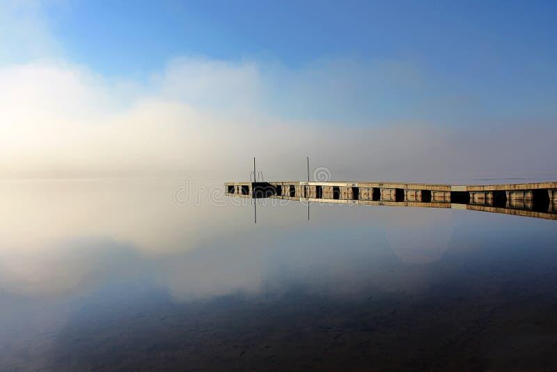 Dokuje odbicie przy jeziorem w mgłowym ranku obraz stock