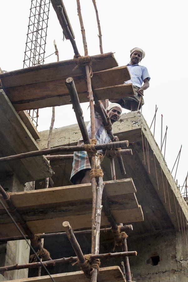 Dokumentär redaktörs- bild En oidentifierad man arbetar på höjder Mycket otrygga scaffoldings royaltyfria bilder