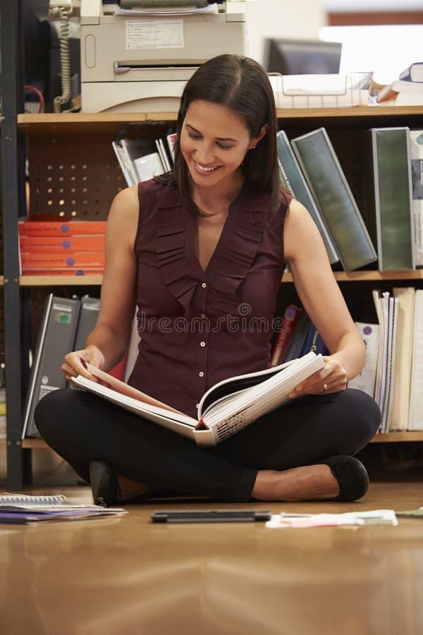Dokument för läsning för affärskvinnaSitting On Office golv royaltyfri foto