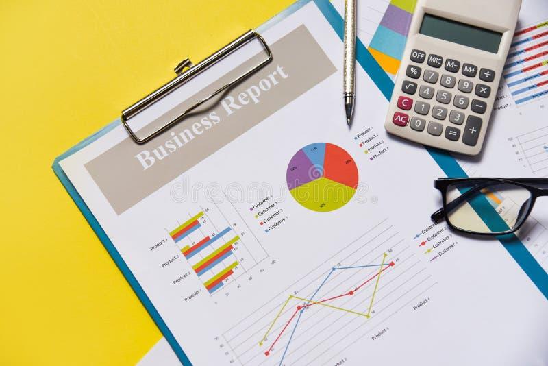 Dokument för papper för rapport för diagram för affärsgraf finansiellt med räknemaskinpennan och gul bakgrund för exponeringsglas royaltyfri fotografi