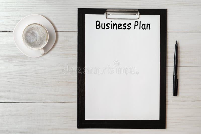 Dokument mit TitelUnternehmensplan und Büroartikel und Cup cofee lizenzfreie stockbilder