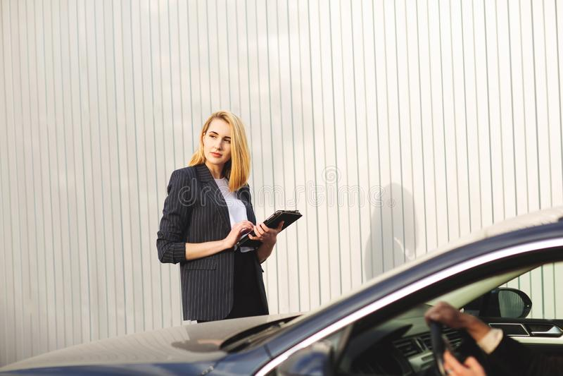 Dokumente, die durch den Frauenangestellten, nahe dem schwarzen Auto überprüfen stockbild