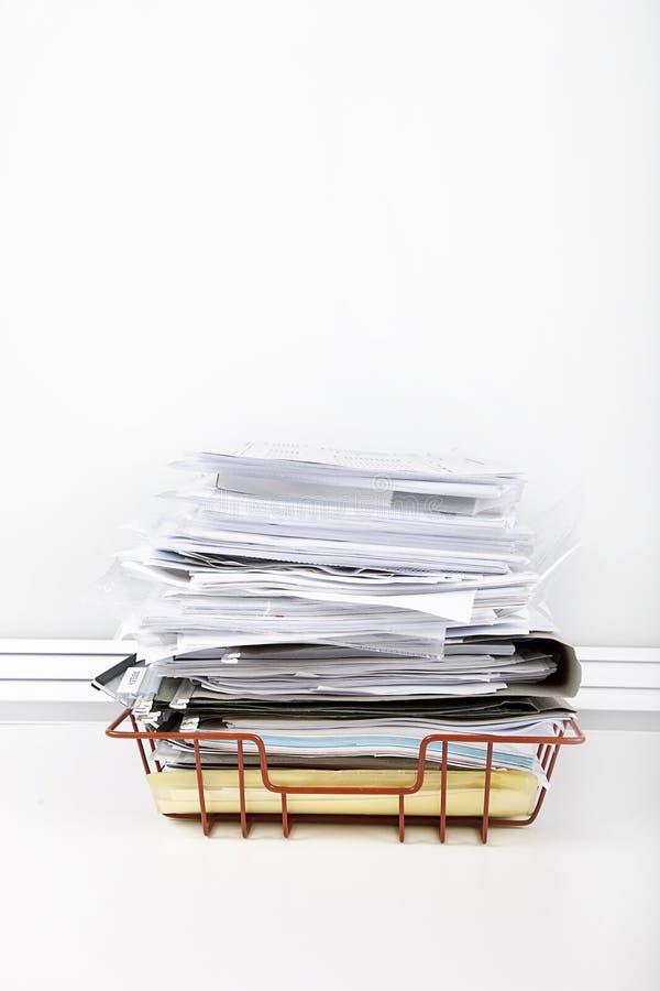 Dokumente, die in Schreibtischbehälter gegen weiße Wand überlaufen stockfoto