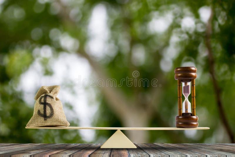 dolar amerykański w workowej torbie, Hourglass stawiający na skalach na drewno stole zdjęcie stock