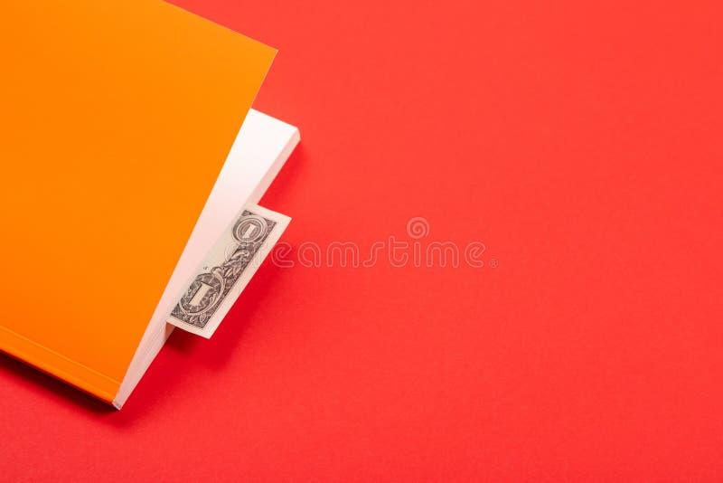 Dolar jako bookmark w pomarańczowej książce odizolowywającej na czerwonym tle obrazy royalty free