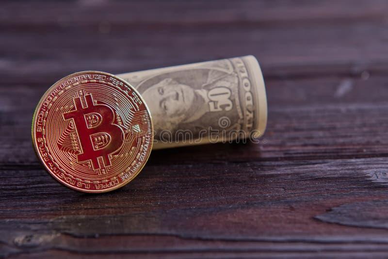 Dolarowi banknoty i Bitcoins na drewnianym stole zdjęcia stock