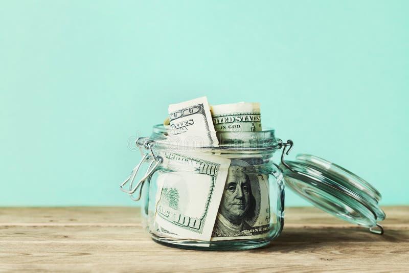 Dolarowi rachunki w szklanym słoju na drewnianym stole monet pojęcia ręk pieniądze stosu chronienia oszczędzanie