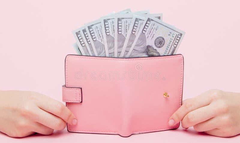 Dolary i różowy portfel w kobiety ` s ręce na różowym tle z kopii przestrzenią obrazy stock