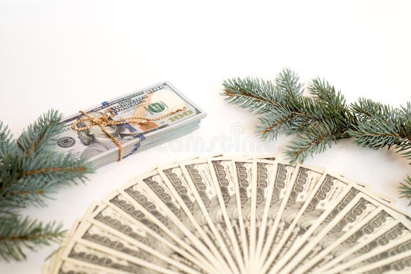 dolary jako prezent dla bożych narodzeń złocisty łańcuch i mnóstwo pieniądze na białym tle i gałąź świerczyna blisko fotografia stock