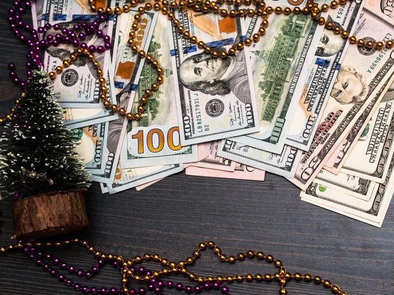 Dolary pieniądze kłaść w Bożenarodzeniowych jedlinowych gałąź na burnt drewnianej deski powierzchni tle dekoracje świąteczne ekol zdjęcia stock