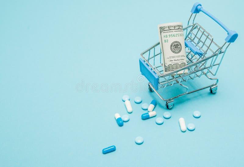Dolary, pigułki i wózek na zakupy na błękitnym tle, Apteki pojęcie kosmos kopii zdjęcia stock