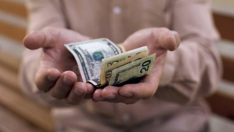 Dolary w starych męskich rękach, niska stopa życiowa, emerytalny ubóstwo, emerytura fotografia stock