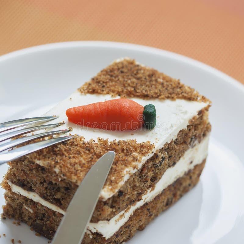 Dolce alle carote casalingo con le decorazioni della carota sul primo piano bianco del piatto, forcella, coltello, fuoco selettiv fotografie stock libere da diritti