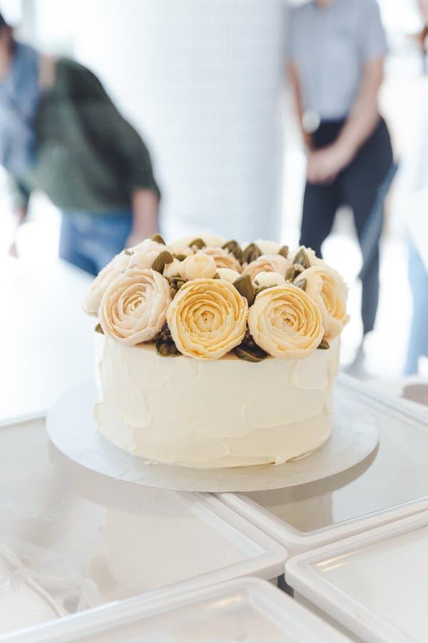 Dolce bianco con i fiori della crema del burro decorati sul supporto fotografia stock
