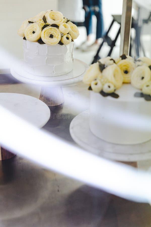Dolce bianco con i fiori della crema del burro decorati sul supporto con la traccia leggera in priorità alta fotografia stock