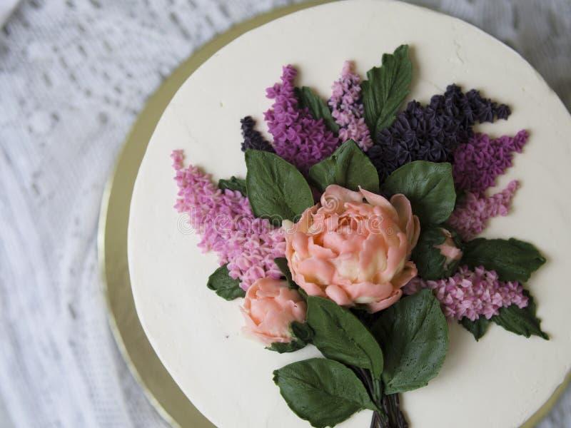 Dolce bianco decorato con i fiori del buttercream - lillà, peonie - su fondo di legno con il tessuto del pizzo Annata, retro Rega fotografia stock libera da diritti