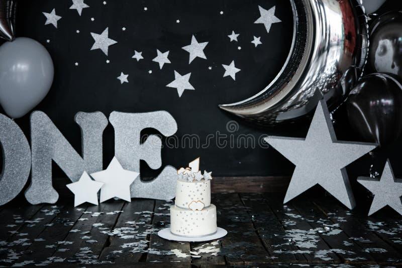 Dolce bianco di primo compleanno con le stelle e la candela per il piccolo neonato e decorazioni per moneta falsa del dolce Il gr immagini stock