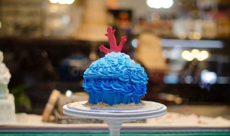 Dolce blu del buttercream con l'ancora rossa davanti al dolce-deposito fotografie stock