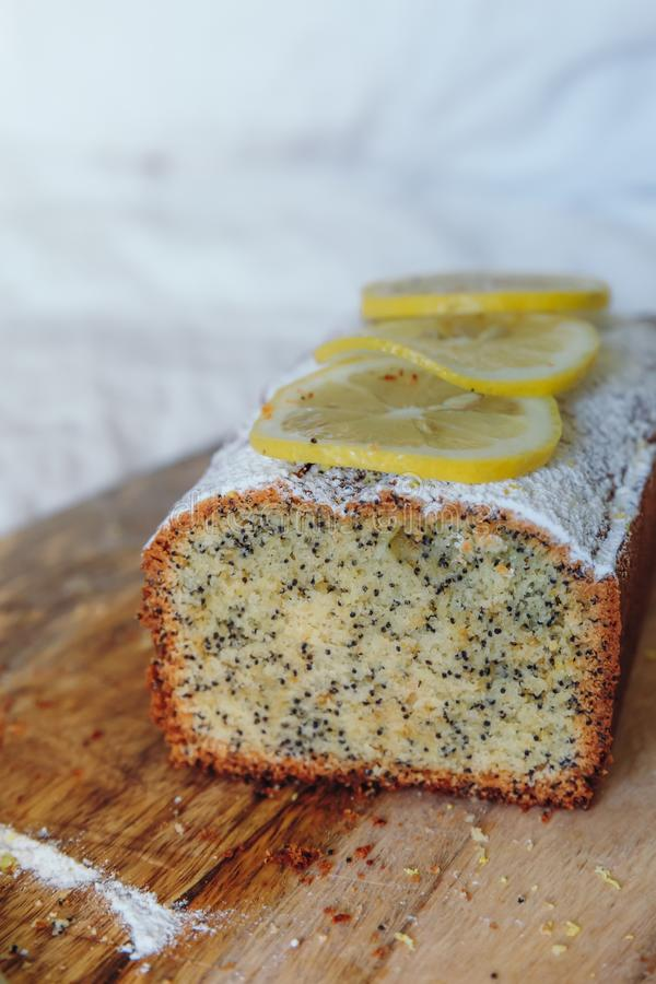 Dolce con i semi di papavero e la scorza di limone, spruzzati con zucchero in polvere Bigné con il limone su un bordo di legno fotografia stock