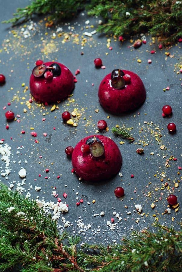 Dolce d'avanguardia della mousse con la glassa della bacca decorata con il mirtillo rosso delle meringhe dell'albero di abete Com fotografia stock libera da diritti