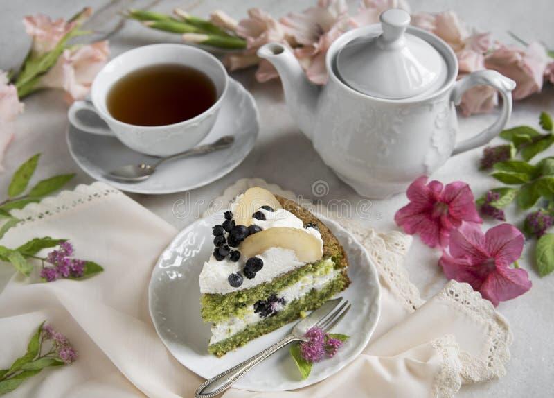 Dolce degli spinaci con la pera, la tazza di tè e la teiera Fiori e tovagliolo su una tavola di marmo immagine stock libera da diritti