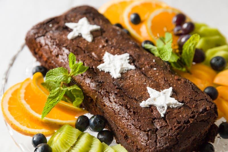 Dolce del brownie del cioccolato con il mirtillo fresco, le stelle dello zucchero bianco e le arance Dolce di cioccolato casaling immagine stock