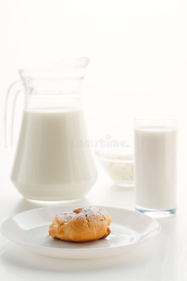 Dolce del Eclair in un piatto, con latte in un vetro ed in una brocca, cottage ch fotografia stock libera da diritti