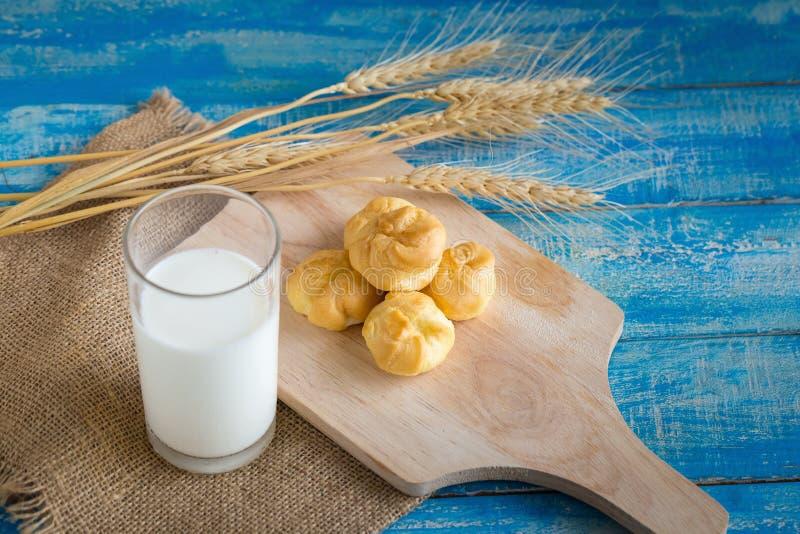 Dolce del Eclair in un piatto di legno con latte in un vetro Foc selettivo immagine stock