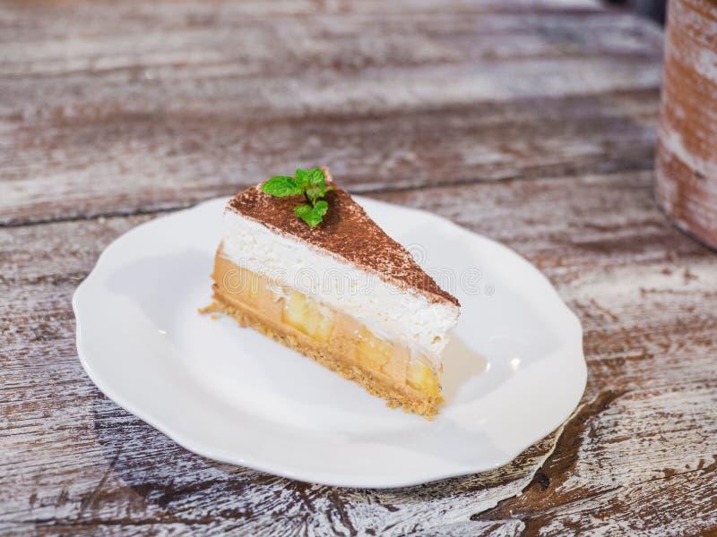 Dolce di banana e caffè alto vicino con le banane, la panna montata, il caramello, il caffè e la caramella sul piatto bianco isol immagini stock