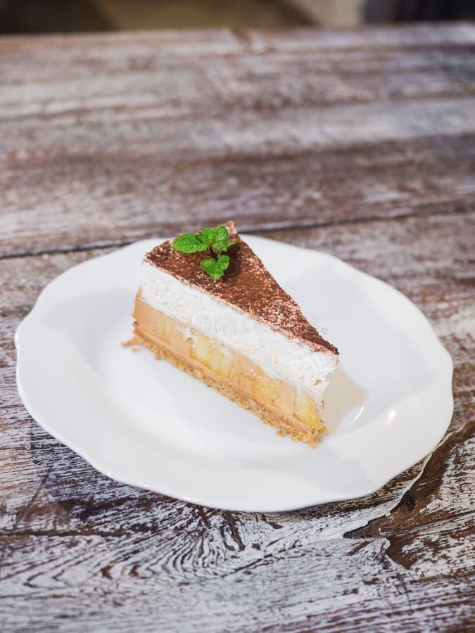 Dolce di banana e caffè alto vicino con le banane, la panna montata, il caramello, il caffè e la caramella sul piatto bianco isol fotografia stock
